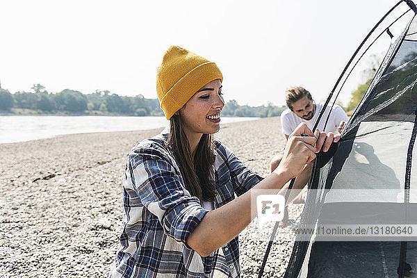 Lächelndes junges Paar baut ein Zelt am Flussufer auf