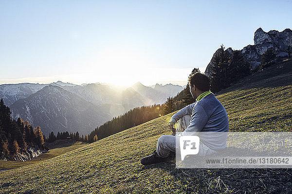 Österreich  Tirol  Rofangebirge  Wanderer bei Sonnenuntergang auf der Wiese sitzend