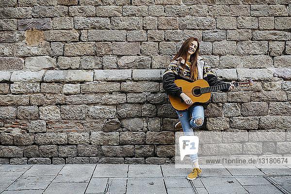 Rothaarige Frau spielt Gitarre in der Stadt