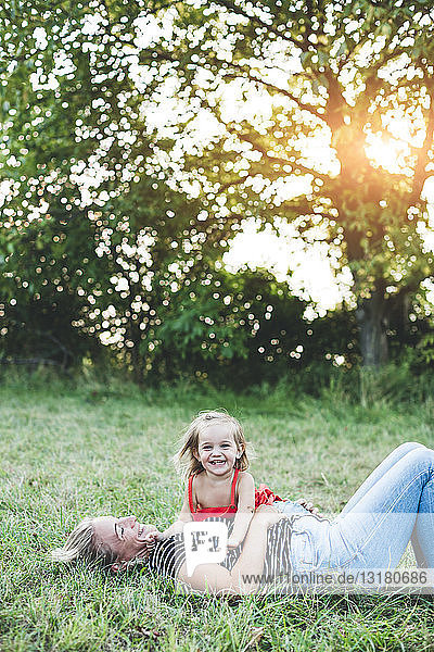 Portrait of happy girl with mother on meadow
