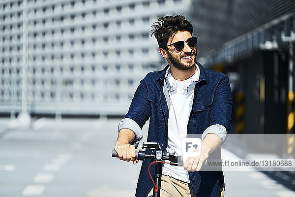 Portrait of smiling man with electric scooter outdoors
