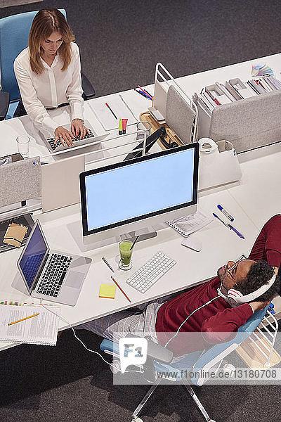 Colleagues working in modern office  man taking a break  listening music