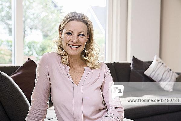 Porträt einer lächelnden Frau  die zu Hause auf der Couch sitzt
