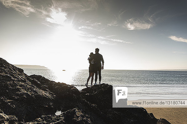 France  Brittany  rear view of young couple standing on rock at the beach at sunset