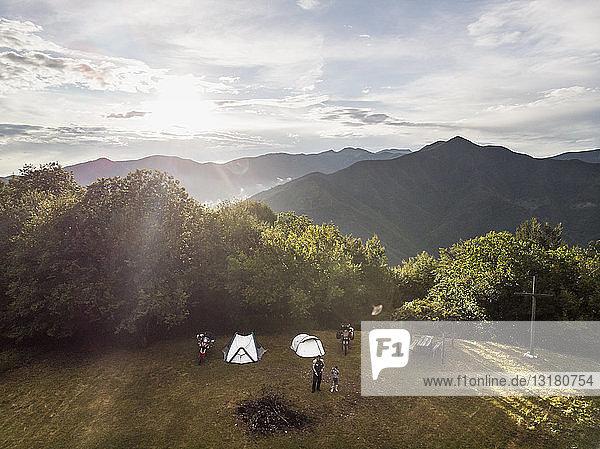 Italien  Toskana  Pistoia  Vater und Sohn auf einer Wiese neben Zelt und Motorrad