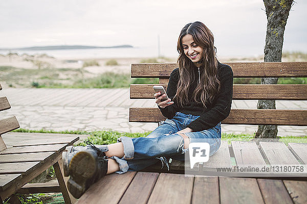 Smiling young woman sitting on bench looking at cell phone