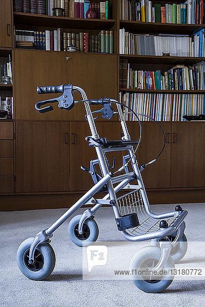 Wlaker auf Rädern vor einem Bücherregal