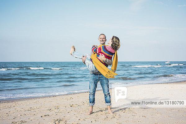 Glücklicher Mann trägt seine Frau auf dem Arm am Strand