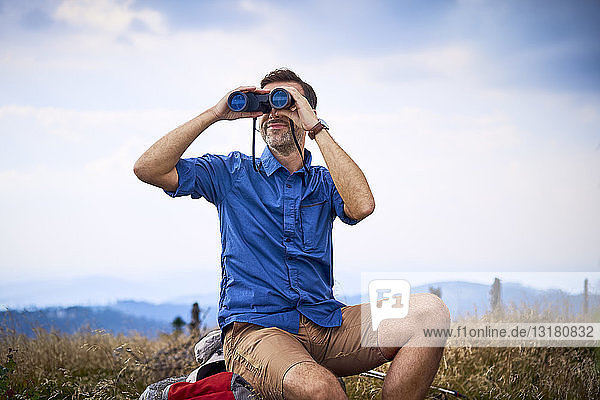 Man looking through binoculars during hiking trip