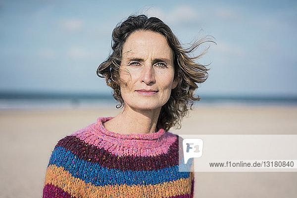Mature woman enjoying the wind on the beach  portrait
