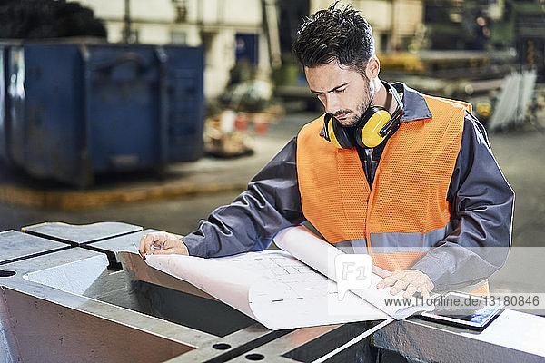Mann in Arbeitsschutzkleidung betrachtet Blaupause in Fabrik