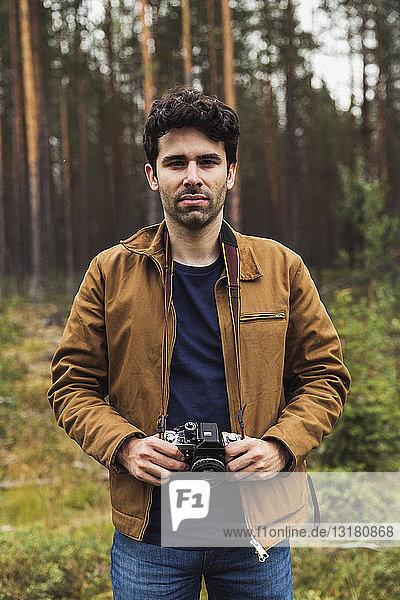 Finnland  Lappland  Porträt eines jungen Mannes mit Kamera in ländlicher Landschaft