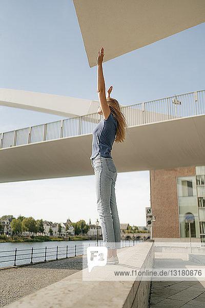 Niederlande  Maastricht  junge Frau steht mit erhobenen Armen auf einer Mauer am Flussufer