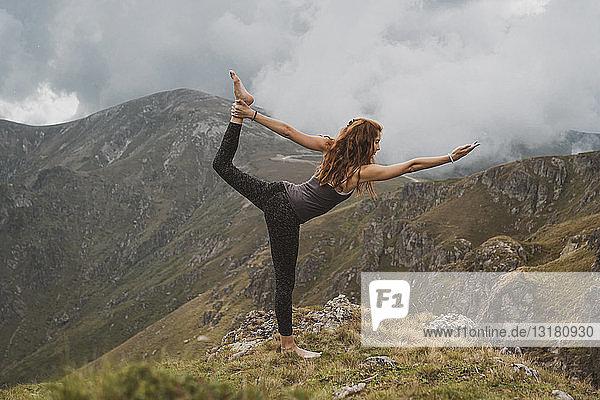 Rothaarige Frau beim Yoga auf dem Gipfel eines Berges  Herr des Tanzes