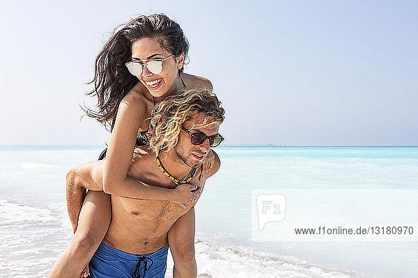 Glückliches Paar am Strand  Mann trägt seine Freundin huckepack