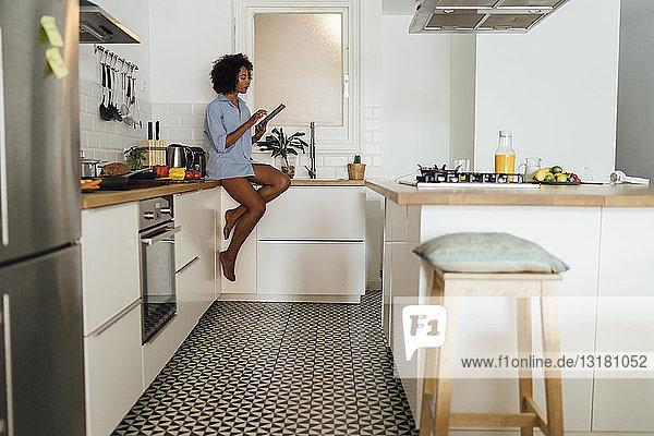 Frau sitzt auf der Arbeitsplatte ihrer Küche und benutzt morgens ein digitales Tablett
