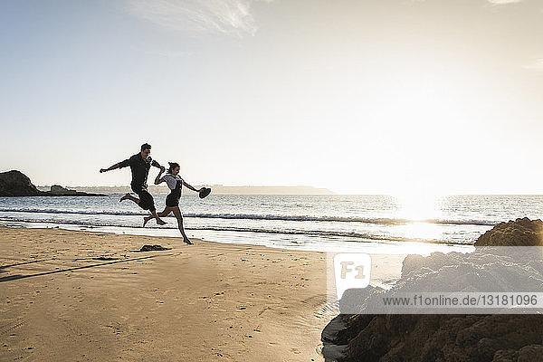 Frankreich,  Bretagne,  glückliches junges Paar springt bei Sonnenuntergang an den Strand