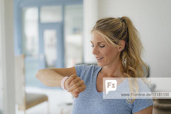 Lächelnde blonde Frau prüft die Zeit