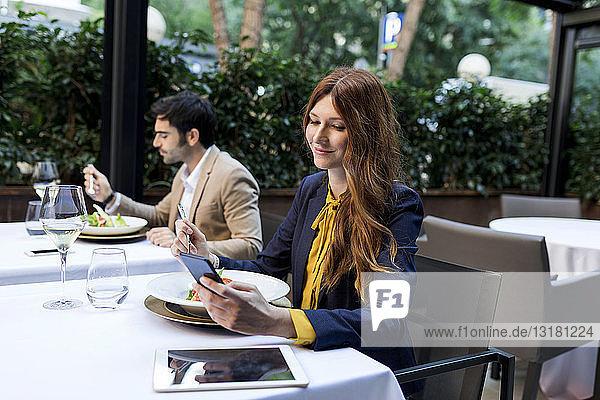 Mann beim Essen und Frau beim Telefonieren in einem Restaurant