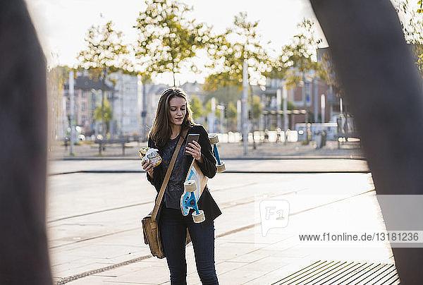 Junge Frau mit Longboard und Snack in der Stadt beim Handy-Check