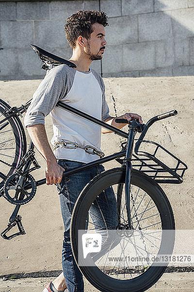 Junger Mann trägt Pendler-Fixie-Fahrrad an Betonmauer