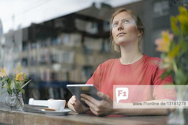 Junge Frau mit Tablette am Fenster in einem Cafe