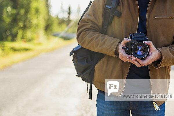 Finnland  Lappland  Nahaufnahme eines Mannes mit Kamera auf der Landstraße