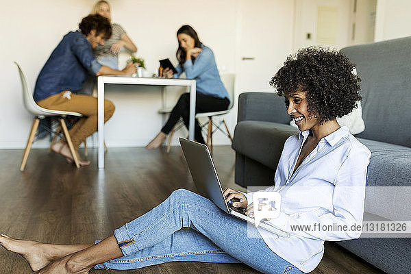 Smiling woman sitting on floor using laptop with friends in background
