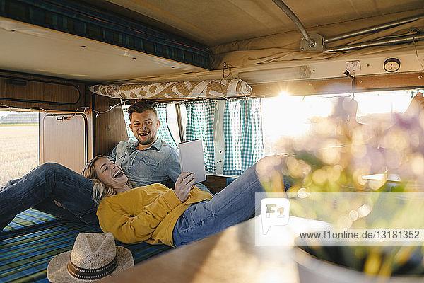 Glückliches junges Paar betrachtet Tablette im Wohnmobil