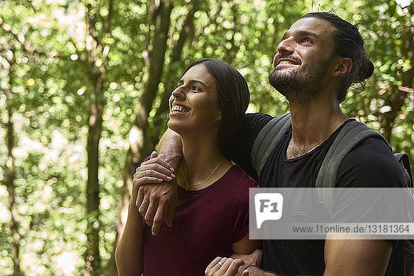 Spanien  Kanarische Inseln  La Palma  glückliches Paar steht in einem Wald und schaut auf