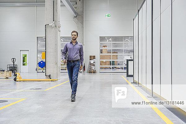 Geschäftsmann geht in einer Fabrikhalle und trägt ein digitales Tablett