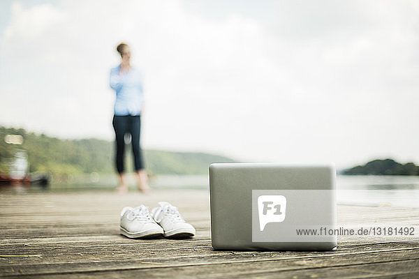 Laptop and shoes on jetty at a lake with woman in background