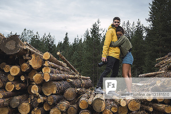 Young woman embracing man with camera on stack of wood