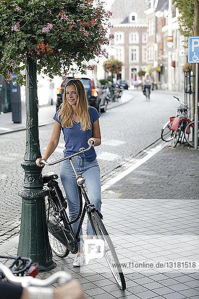 Niederlande  Maastricht  junge Frau mit Fahrrad in der Stadt