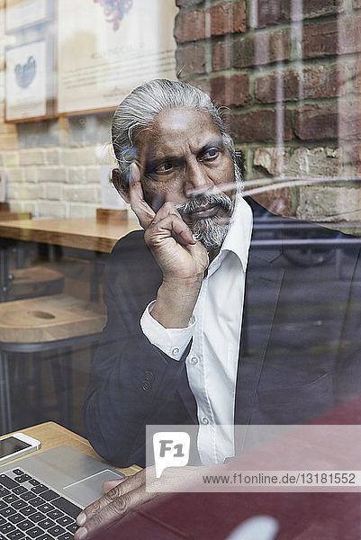 Portrait of pensive senior businessman in a coffee shop looking out of window
