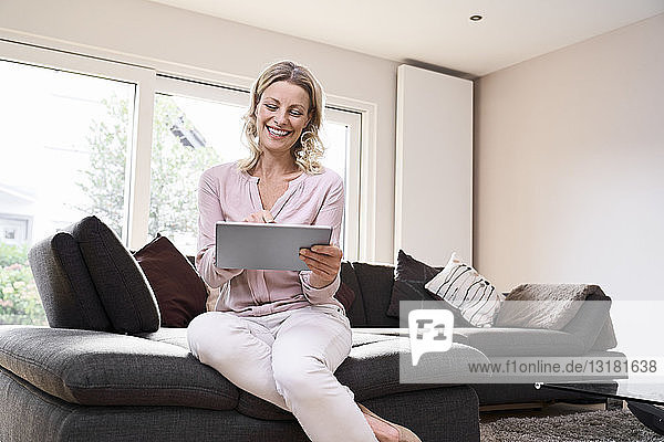 Happy woman sitting on couch using tablet at home