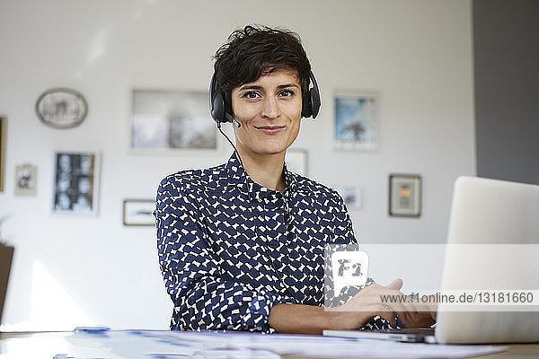 Porträt einer lächelnden Frau zu Hause mit Headset und Laptop