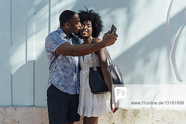 Young couple kissing and taking a selfie