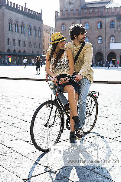 Italy  Bologna  young couple on bicycle watching something