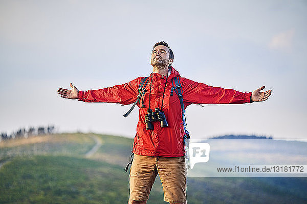 Man standing with outstretched arms on mountain top