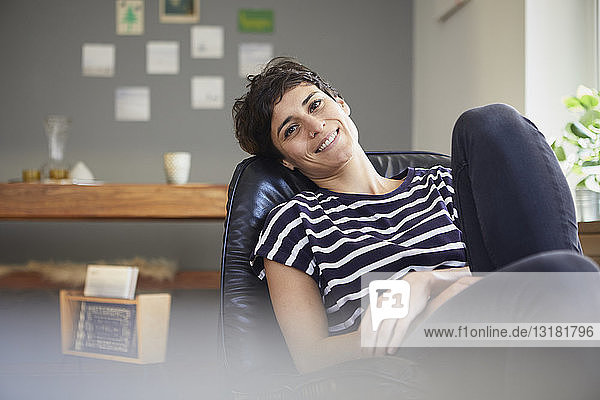Portrait of smiling woman sitting at home relaxing