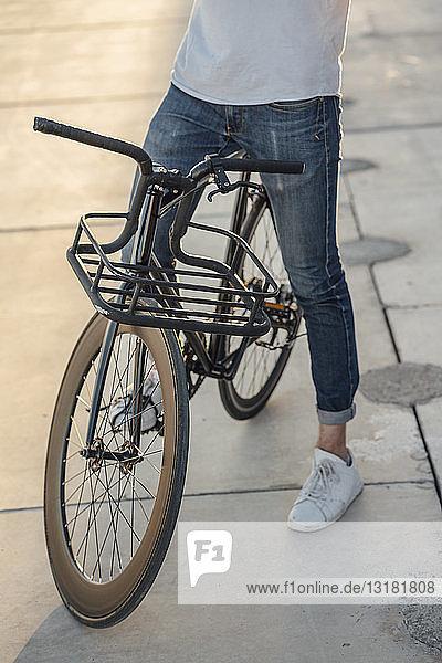 Nahaufnahme eines Mannes mit Pendler-Fixie-Fahrrad auf Betonplatten