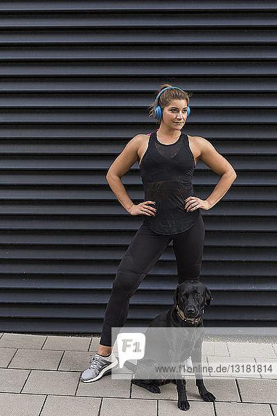 Porträt einer jungen Frau mit Kopfhörer und Hund im Freien