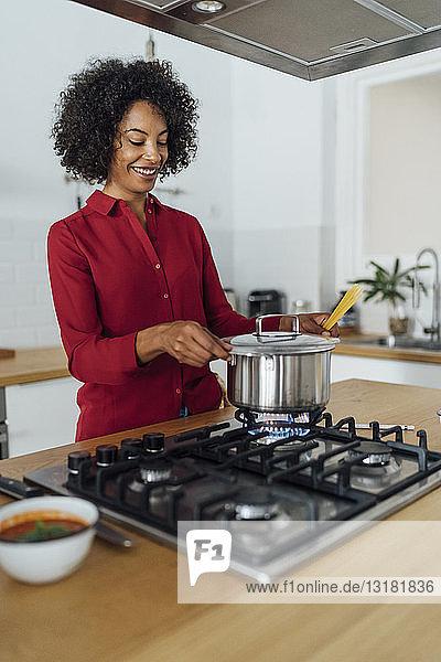 Woman standing in kitchen  preparing food