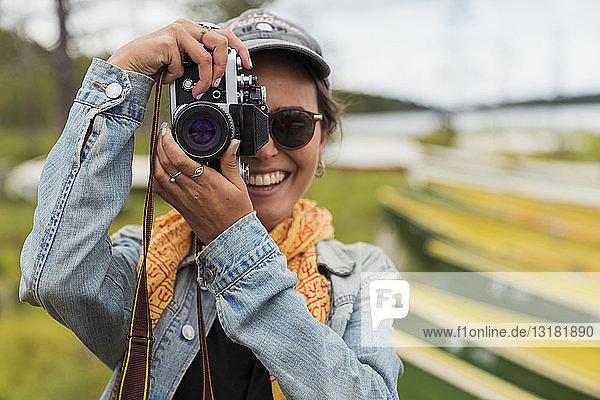 Finnland  Lappland  Porträt einer lächelnden jungen Frau  die mit einer Kamera am Seeufer fotografiert