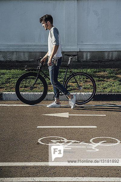 Junger Mann schiebt Pendler-Fixie-Rad auf Fahrradweg