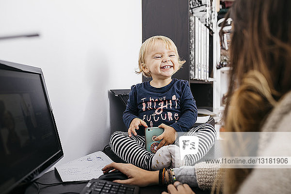 Mother working at home with little daughter sitting on desk