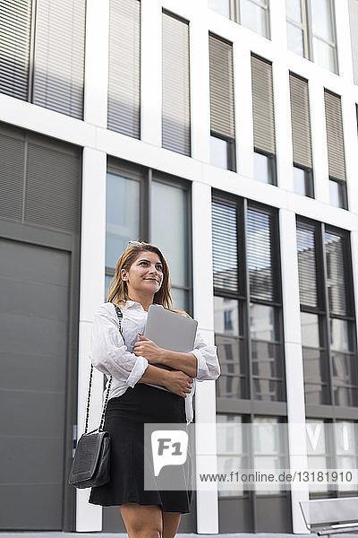 Porträt einer lächelnden Geschäftsfrau mit Laptop im Freien