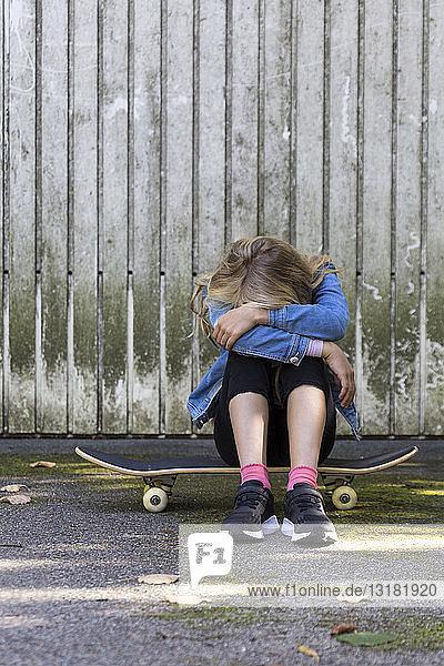 Girl sitting on her skateboard outdoors hiding her face