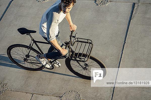 Junger Mann fährt Pendler-Fixie-Bike auf Betonplatten